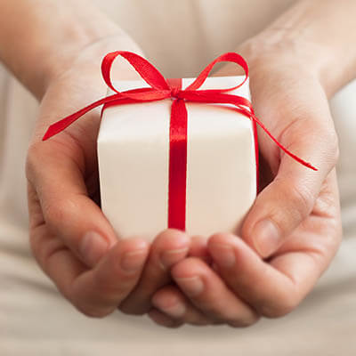 A small gift wrapped in a red ribbon