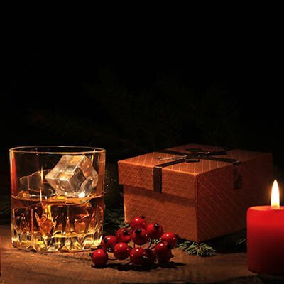 A glass of whiskey next to a wrapped gift and lit candle