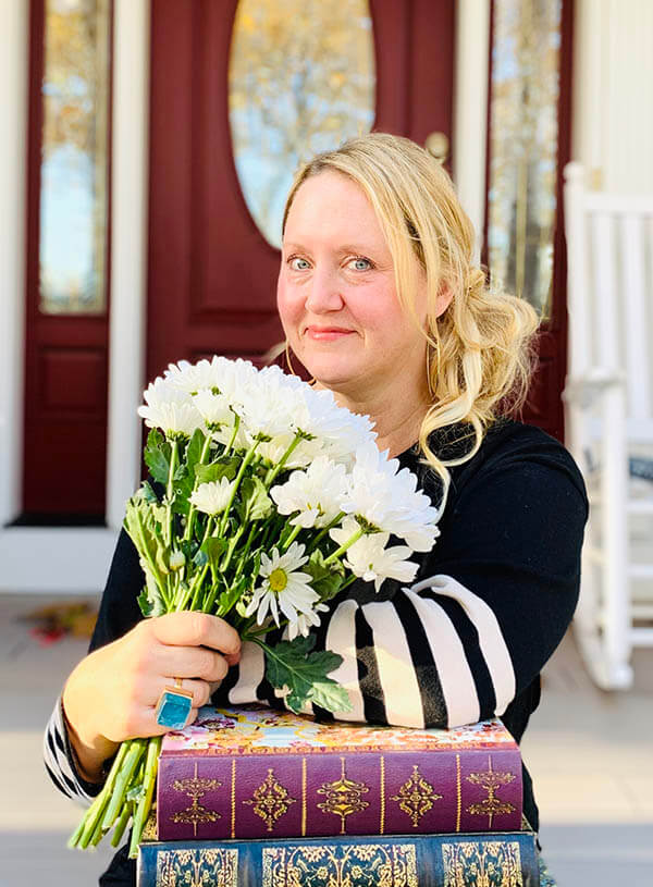Kelly Fredericks sitting on her porch with flowers and books