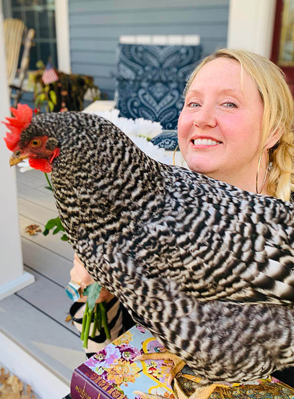 Kelly Fredericks on her porch with a chicken