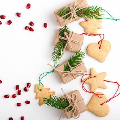 Pomegranate seeds and a string of Christmas cookies on a white background