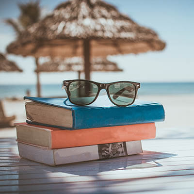 Books stacked on a table on a beach with sunglasses on top