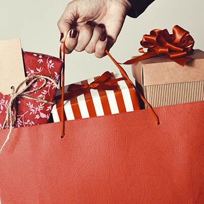 A red shopping bag full of wrapped gifts