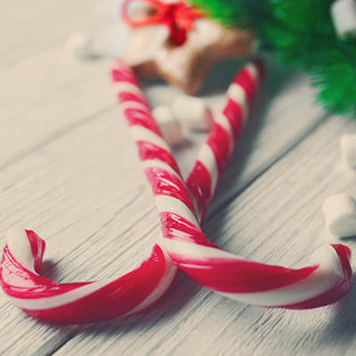 Two candy canes crossed on a white wooden table