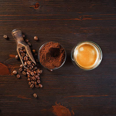 espresso beans, ground espresso and a cup of espresso on a wooden table