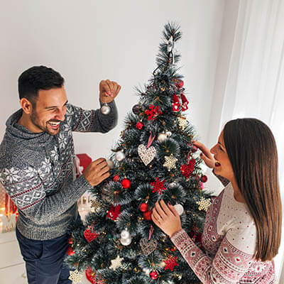 Couple trimming a Christmas tree
