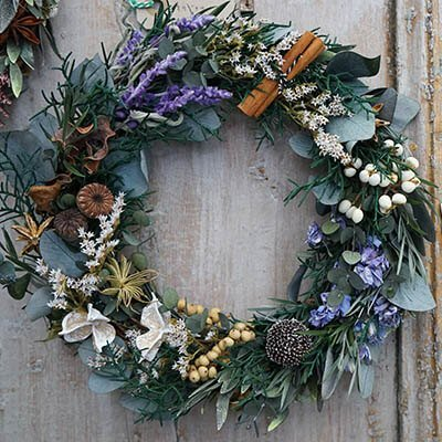 A blue, green and gold wreath on a wooden door